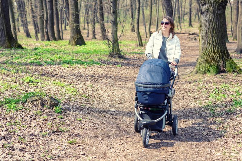 Beautiful young adult woman walking with baby in stroller through forest or park on bright sunny day. Healthy lifestyle and. Children healthcare. Happy royalty free stock images