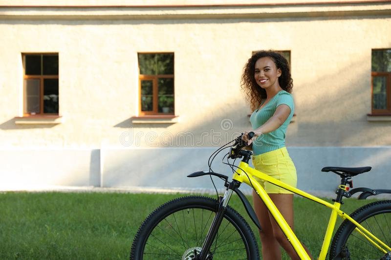 young African-American woman with bicycle on city street royalty free stock images