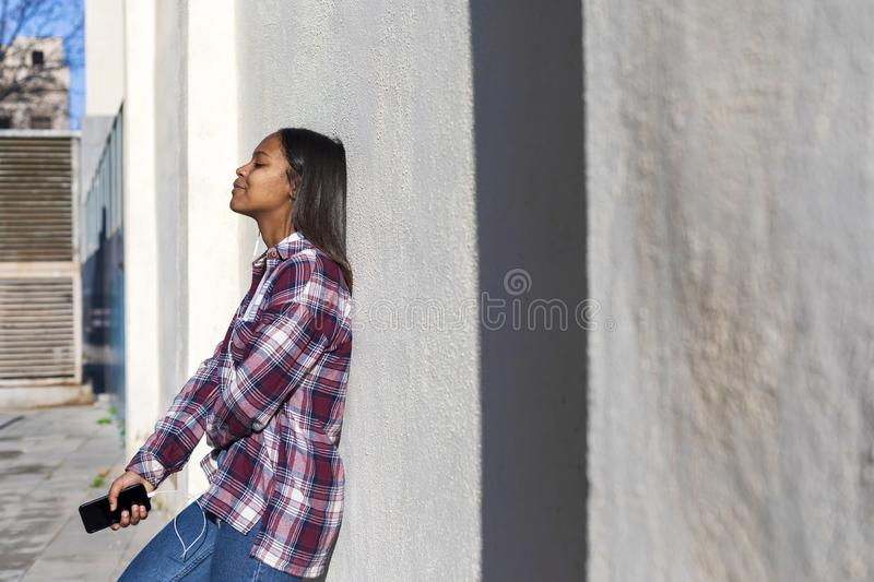 Beautiful young african american woman leaning on a white wall outdoors in the street while holding a phone and listening music by royalty free stock images