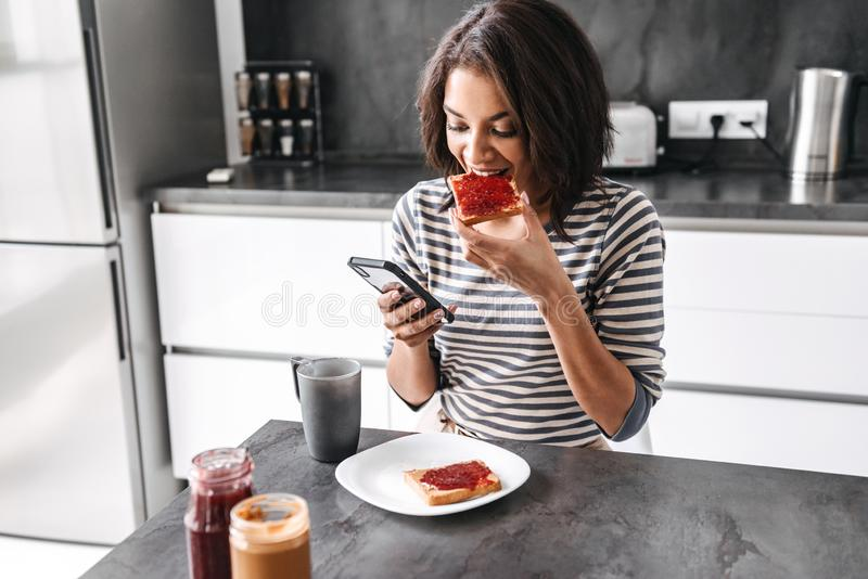 Beautiful young african woman having breakfast. While sitting at the kitchen, using mobile phone stock images