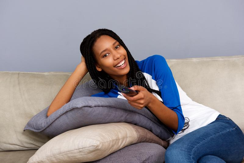 Beautiful young african woman holding remote control relaxing on at sofa and watching tv stock images
