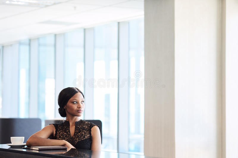 Beautiful young african woman looking thoughtfully off into the distance. Beautiful young black woman looking off into the distance, while seated at a counter in stock photo