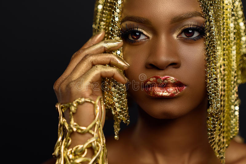 Beautiful young african woman posing at studio in golden jewellery, face with hand portrait over dark background stock image