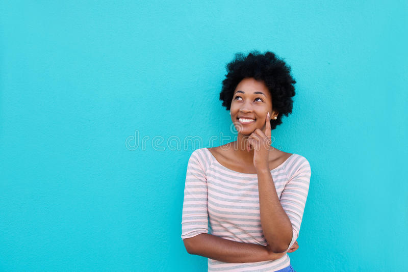 Beautiful young african woman smiling and thinking royalty free stock photos