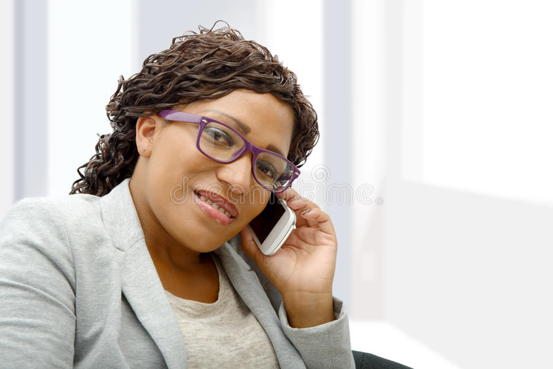 Beautiful young african woman talking on cell phone royalty free stock photography