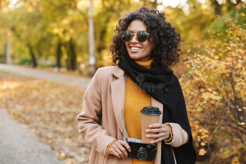 Beautiful young african woman walking outdoors in a spring park drinking coffee stock image