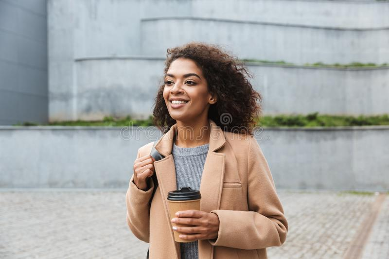 Beautiful young african woman wearing coat walking. Outdoors, holding takeaway cup stock photography