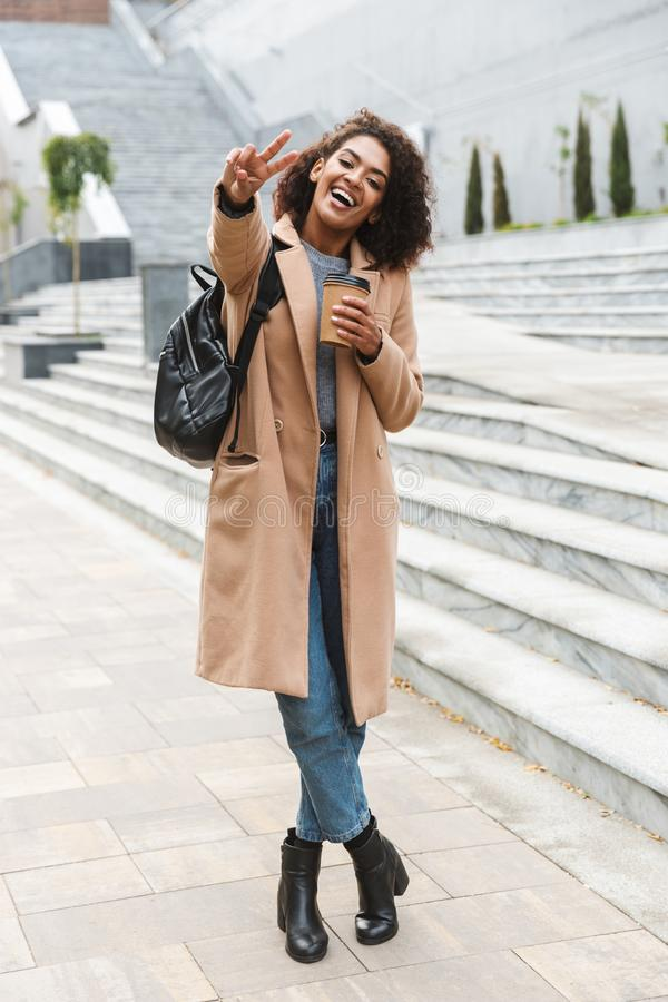 Beautiful young african woman wearing coat walking. Outdoors, holding takeaway cup royalty free stock image