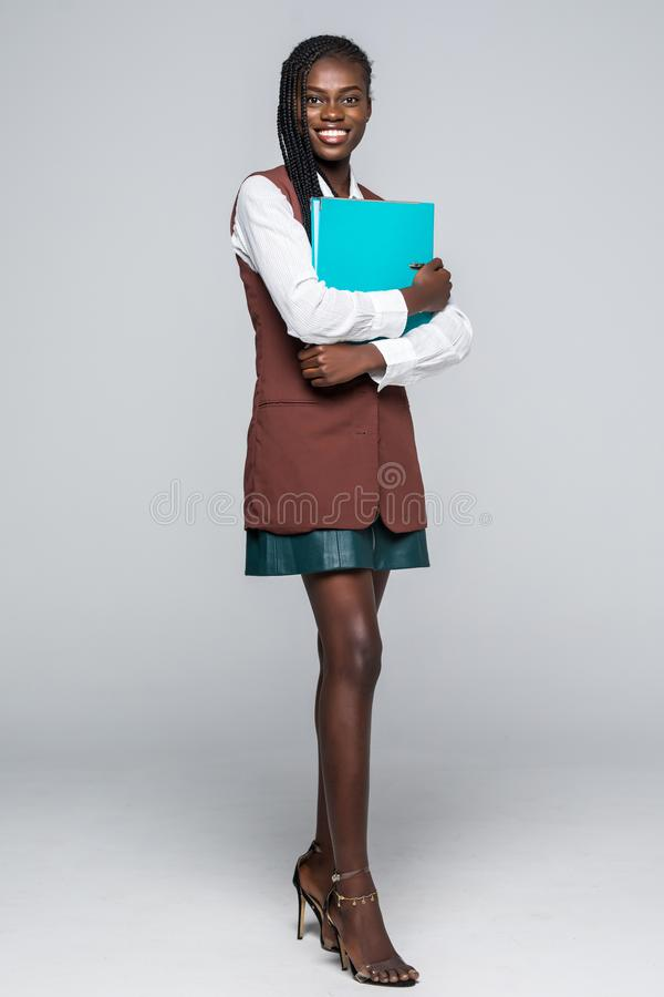 Beautiful young Afro American business woman in formal wear is holding a folder, looking at camera and smiling on gray background stock photos