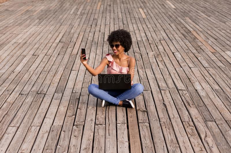 beautiful young afro american woman using laptop, Sitting on wood floor and smiling. wood background. Lifestyle outdoors royalty free stock image