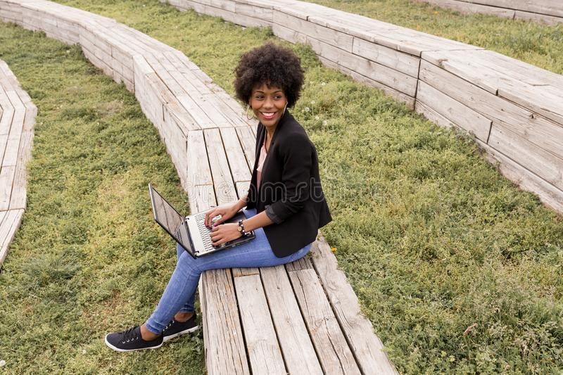 Beautiful young afro american woman using laptop, Sitting on wood stairs and smiling. wood background. Lifestyle outdoors stock photo