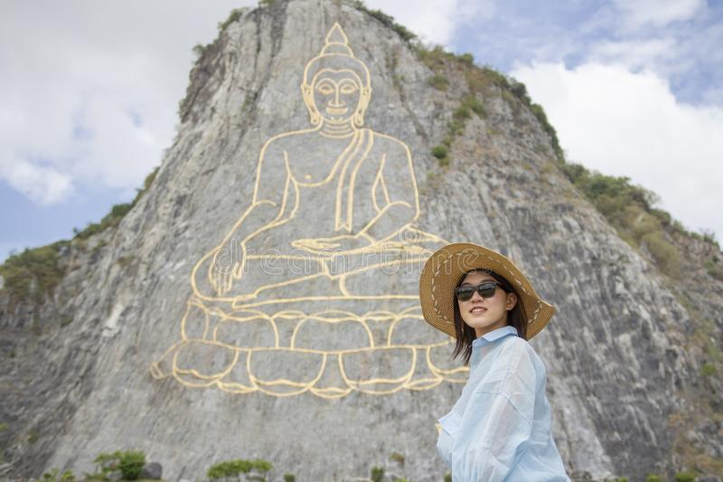 Beautiful young aisan woman is standing and smile on the background of mountain with golden statue of buddha on a hillside, Buddha royalty free stock photography
