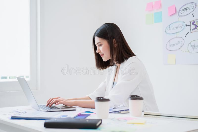 Beautiful young asian business woman looks happy and concentrate working with her laptop while sitting in the white office in good stock photos