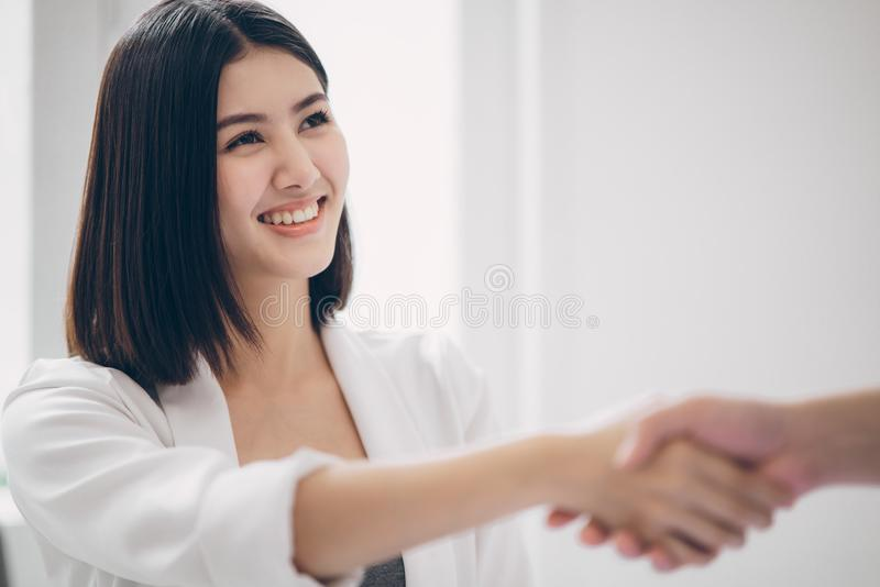 Beautiful young asian business woman smiling with triumphant of the success deal or project while shaking hand with business man royalty free stock image