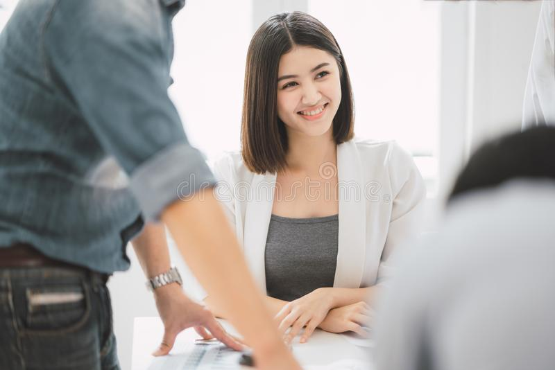 Beautiful young asian business woman wearing white suit smile and sitting among colleague while discussion about the project in royalty free stock photography