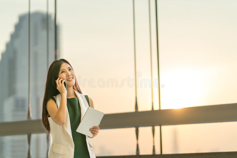 Beautiful young Asian businesswoman use smartphone and digital tablet look upward to copy space royalty free stock photo