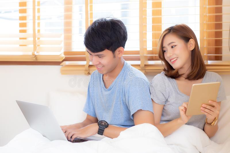 Beautiful young asian couple cheerful freelance working with man using laptop and woman using tablet on couch. Beautiful young asian couple cheerful freelance royalty free stock photo