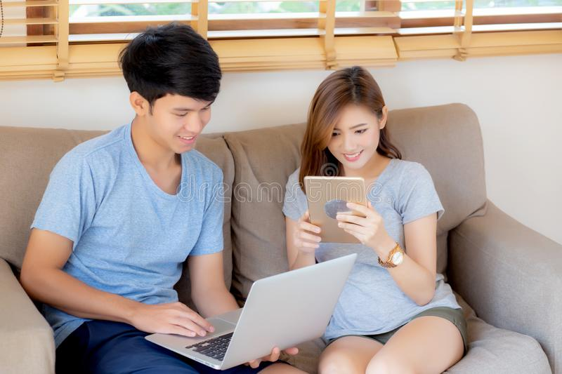 Beautiful young asian couple cheerful freelance working with man using laptop and woman using tablet on couch. Beautiful young asian couple cheerful freelance royalty free stock image