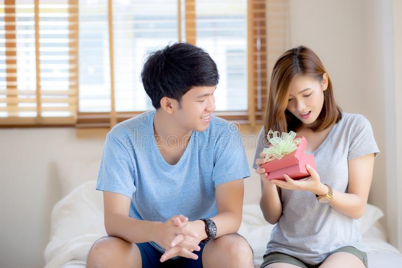 Beautiful young asian couple in love surprise gift box in bedroom at home, family anniversary with enjoy and romantic together stock photos