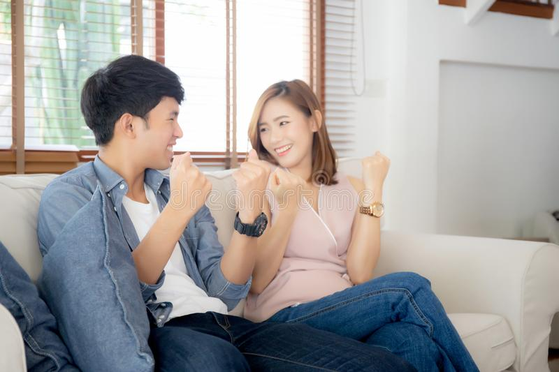 Beautiful young asian couple man and woman gesture together with relax after work success on sofa royalty free stock images