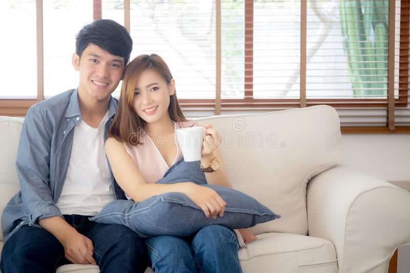 Beautiful young asian couple smiling and talking story married sitting on sofa at home together stock image