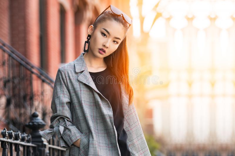 Beautiful young Asian fashion model woman walking out from home in big city at sunny day. stock images