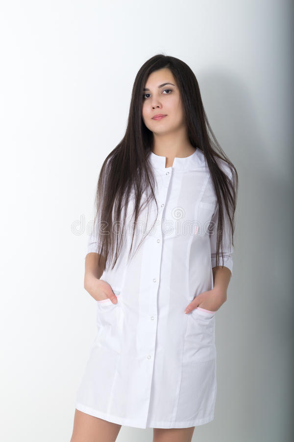 Beautiful young asian female doctor in medical gown holding a phonendoscope. Beautiful young asian female doctor in medical gown holding phonendoscope stock images