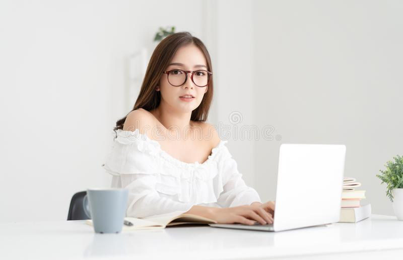 Beautiful young Asian female student using laptop and looking at camera while sitting in living room at home. Education, stock photography