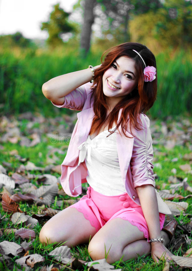 Beautiful young Asian girl in the grass royalty free stock image