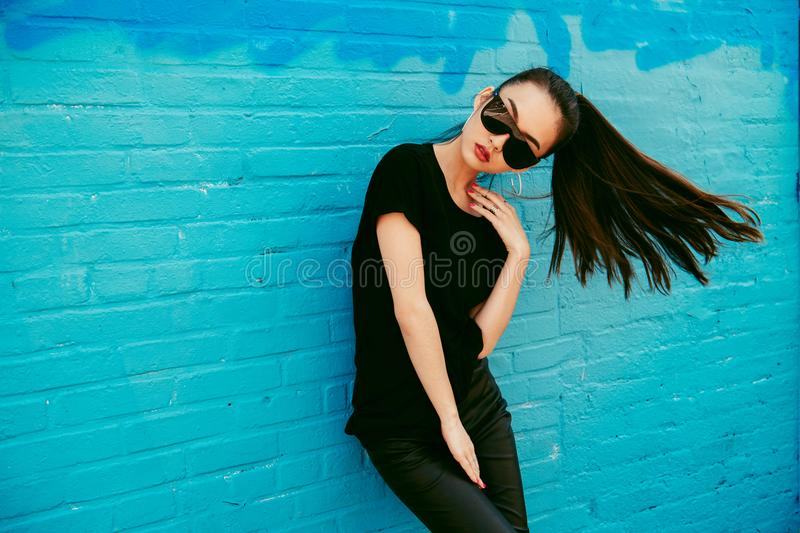 Beautiful young asian girl with long hair wearing sunglasses and black t-shirt posing in front of blue wall. Beautiful young asian girl with long hair wearing royalty free stock image