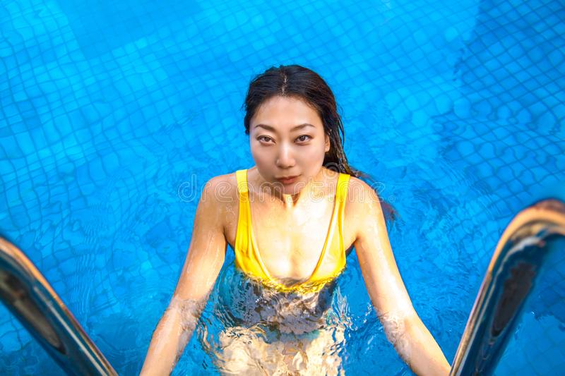 Beautiful young asian girl relaxing in the swimming pool outdoors. Wonderful day. Beautiful young asian girl relaxing in the swimming pool outdoors, copy space stock photos