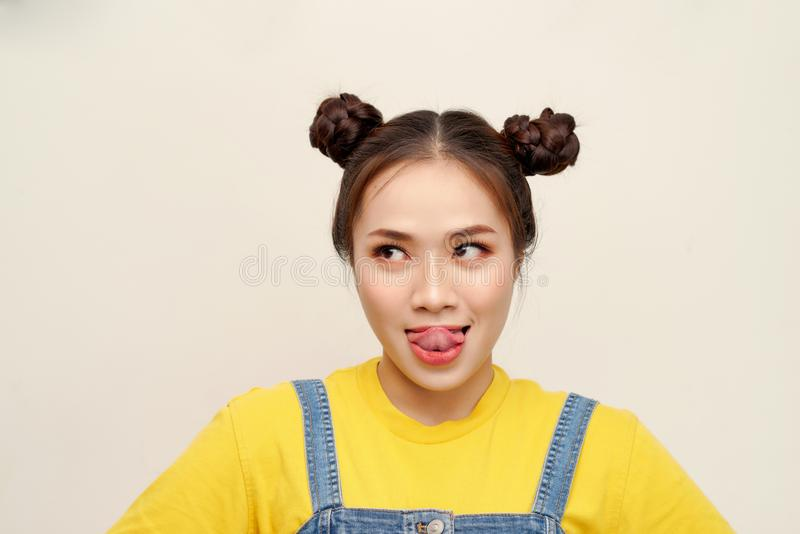 Beautiful young Asian girl wearing jeans dungaree with two buns hair on white background royalty free stock images