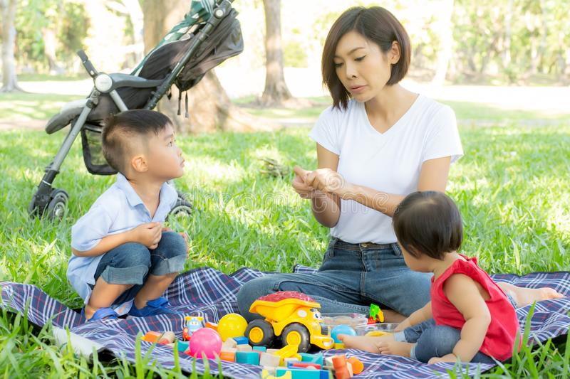 Beautiful young asian mom and daughter playing toy blocks for learning development happy and fun at park in summer royalty free stock photography