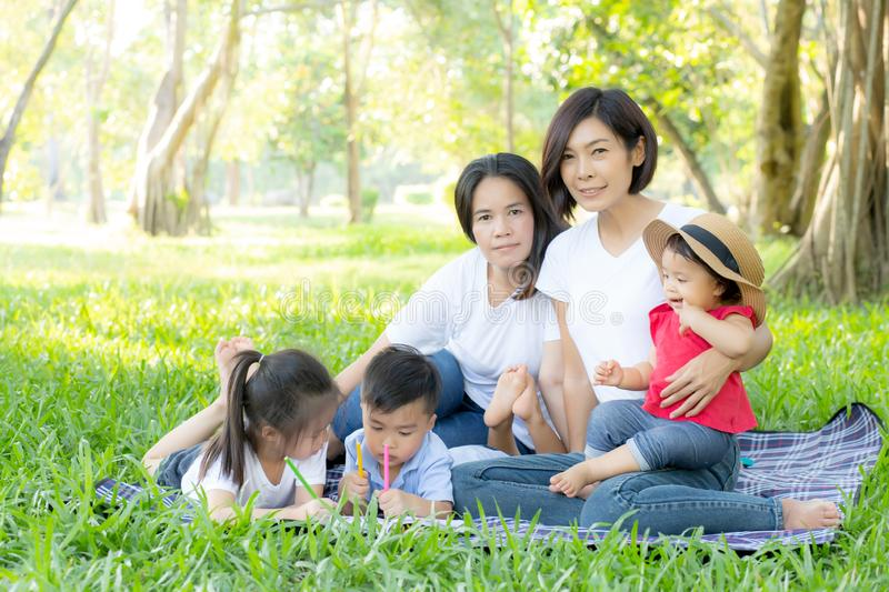 Beautiful young asian parent family portrait picnic in the park, kid or children and mother love happy and cheerful together. In summer at garden, lifestyle royalty free stock photos