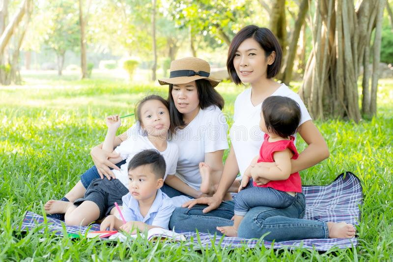Beautiful young asian parent family portrait picnic in the park, kid or children and mother love happy and cheerful together. In summer at garden, lifestyle royalty free stock photography