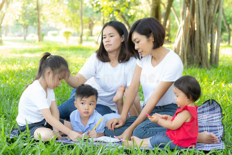 Beautiful young asian parent family portrait picnic in the park, kid or children and mother love happy and cheerful together. In summer at garden, lifestyle stock images