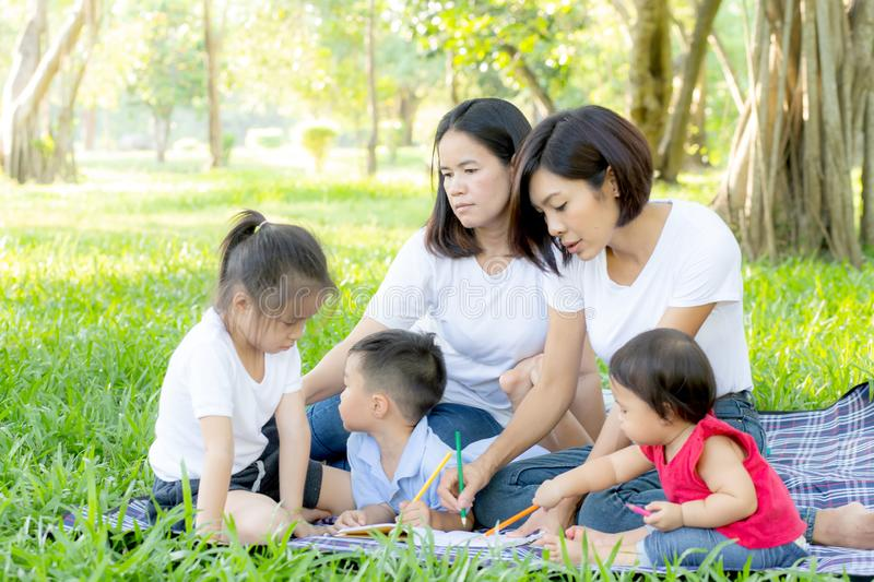 Beautiful young asian parent family portrait picnic in the park, kid or children and mother love happy and cheerful together. In summer at garden, lifestyle royalty free stock image