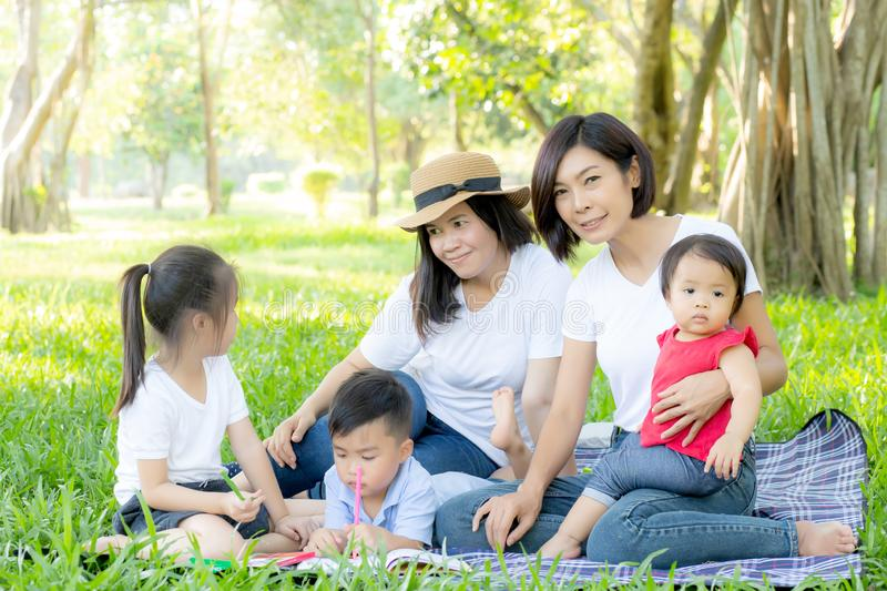 Beautiful young asian parent family portrait picnic in the park, kid or children and mother love happy and cheerful together royalty free stock photos
