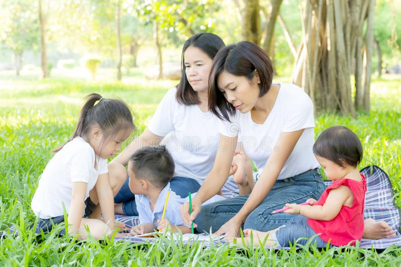 Beautiful young asian parent family portrait picnic in the park, kid or children and mother love happy and cheerful together royalty free stock photography