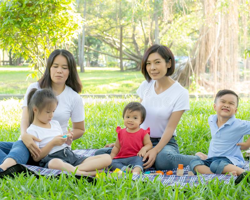 Beautiful young asian parent family portrait picnic in the park, kid or children and mother love happy and cheerful together stock image