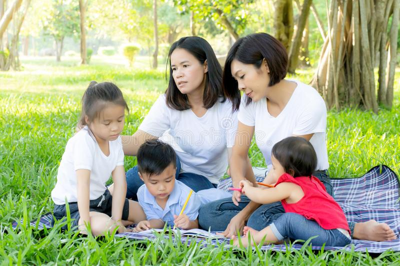 Beautiful young asian parent family portrait picnic in the park, kid or children and mother love happy and cheerful together royalty free stock images