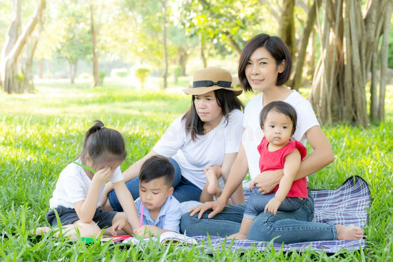 Beautiful young asian parent family portrait picnic in the park, kid or children and mother love happy and cheerful together stock images