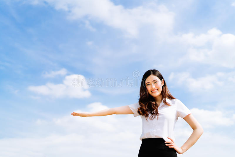 Beautiful young asian university or college student woman doing advertising or product presenting pose, copy space on blue sky stock photo