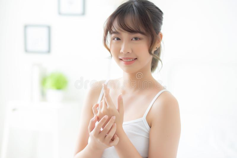 Beautiful young asian woman applying cream and treatment for skin care touch on hand, asia girl with lotion spa and moisturizing royalty free stock photography