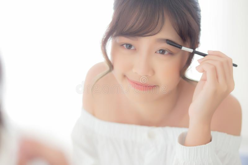 Beautiful young asian woman applying makeup eyebrows brush, beauty asia girl using cosmetic for make up style looking mirror royalty free stock photos