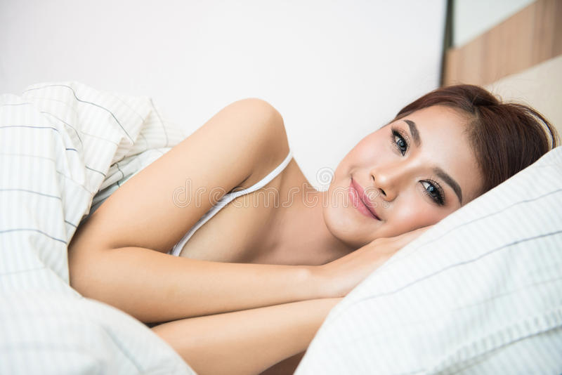 Beautiful young Asian woman on the bed stock photos