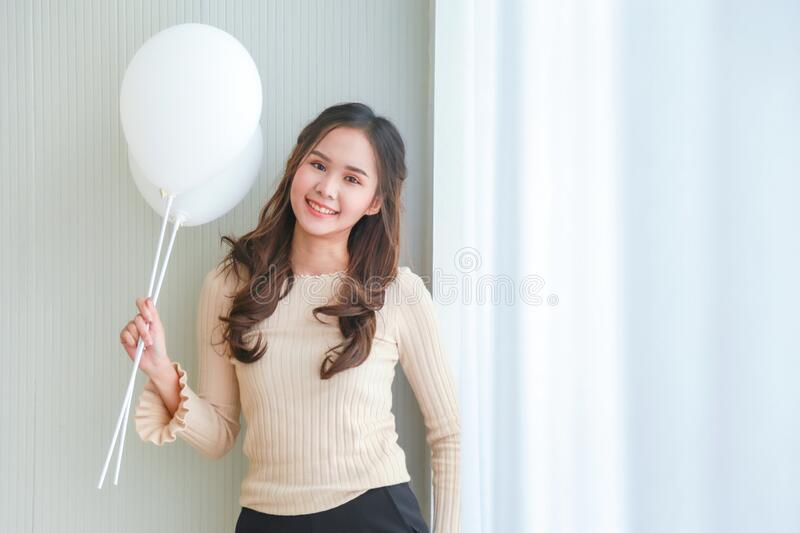 Beautiful young Asian woman in beige casual wear is smiling and holding white balloons side a white blinds. stock images