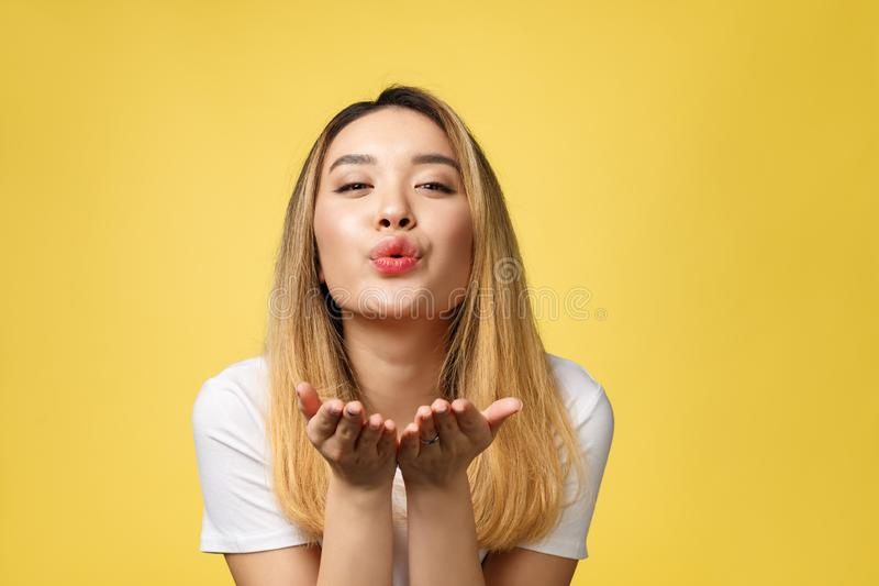 Beautiful young Asian woman blow a kiss isolated on yellow background.  stock photography