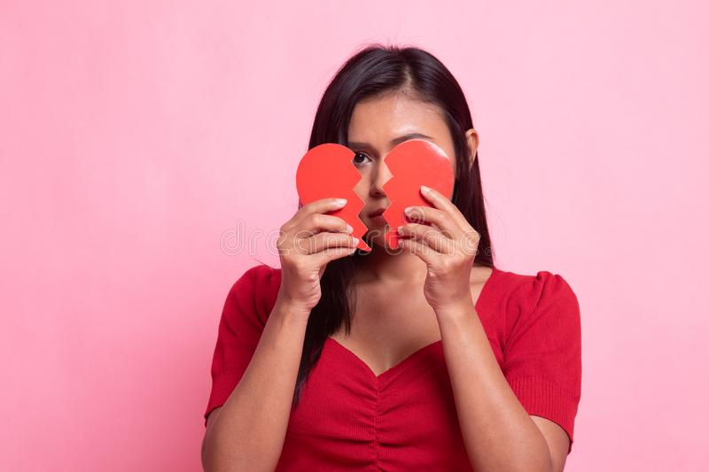 Beautiful young Asian woman with broken heart. On pink background royalty free stock image