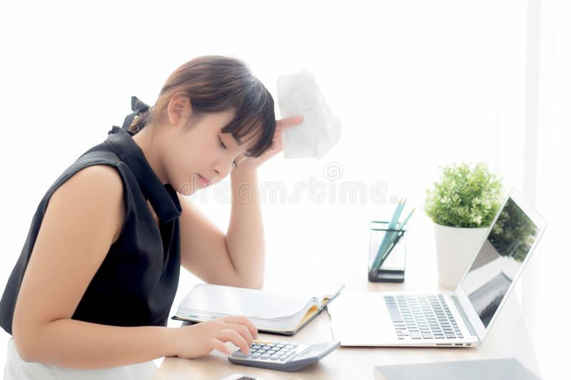 Beautiful young asian woman calculating expenses household and writing notebook on desk. Girl checking bill and stress and note, female worry debt and tax royalty free stock photo